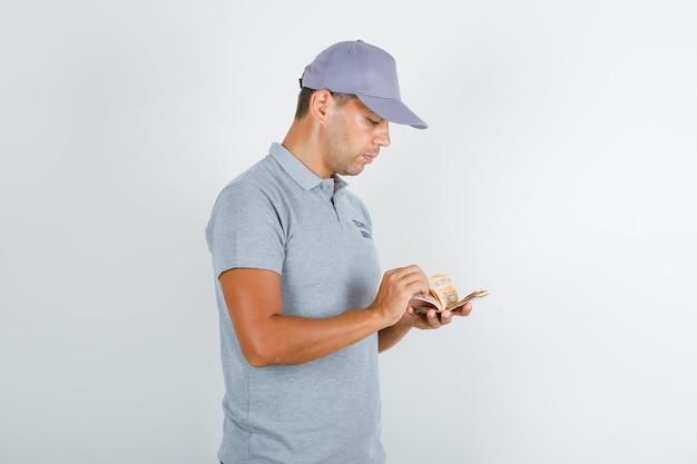 Pracownik obsługi technicznej w szarym t-shircie z czapką liczącą banknoty euro