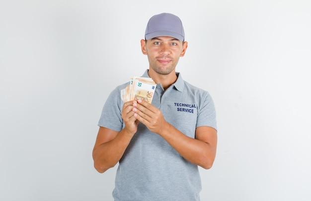 Pracownik obsługi technicznej w szarym t-shircie z czapką z banknotami euro