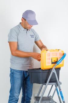 Pracownik obsługi technicznej zaglądający do skrzynki z narzędziami w szarej koszulce z czapką i wyglądający na zajętego