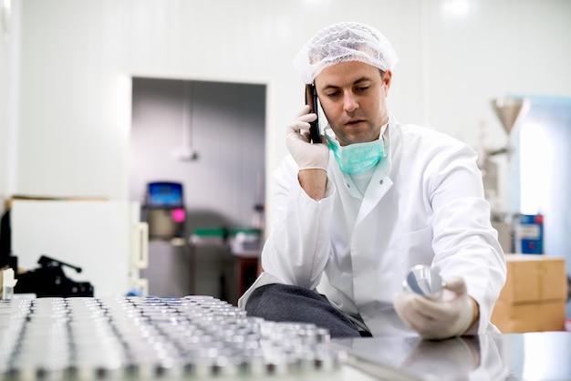Pracownik ochronny w fabryce farmaceutycznej w swoim miejscu pracy rozmawia przez telefon komórkowy.