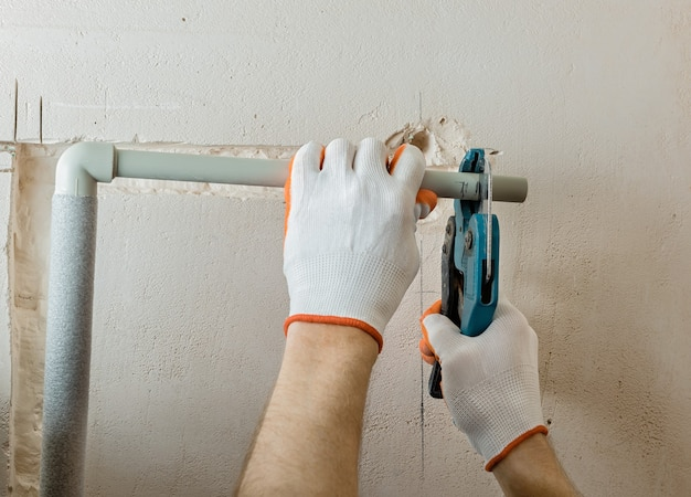 Pracownik odcina część rury nożyczkami do rur