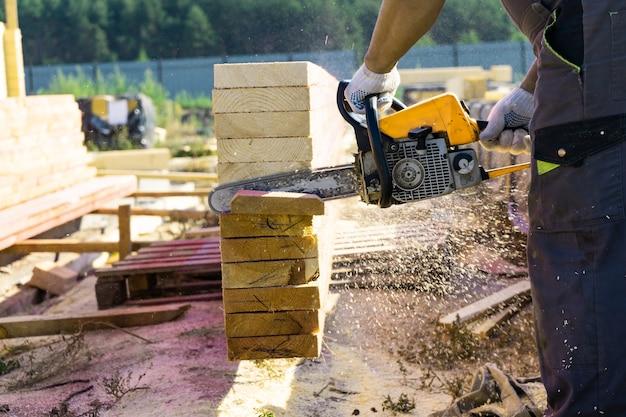 Pracownik odcina drewnianą deskę do pił łańcuchowych. budowa domu.