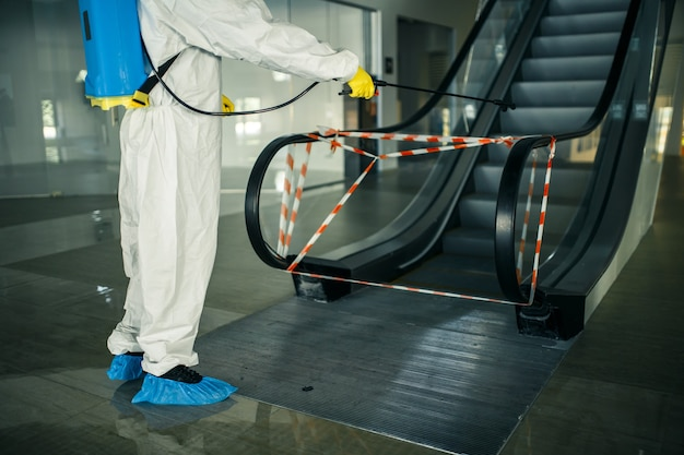 Pracownik odkażający dezynfekuje schody ruchome sprayem w pustym centrum handlowym, aby zapobiec rozprzestrzenianiu się covid-19 w miejscach publicznych. koncepcja opieki zdrowotnej, czystości, izolacji i kwarantanny.