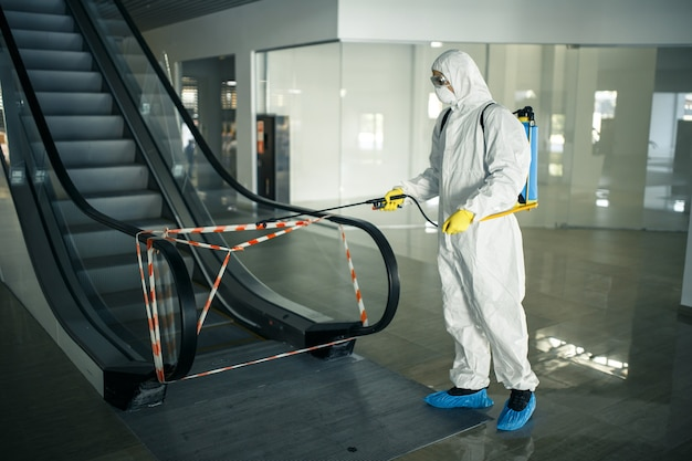 Pracownik odkażający dezynfekuje schody ruchome za pomocą sprayu w pustym centrum handlowym, aby zapobiec rozprzestrzenianiu się covid-19 w miejscach publicznych.