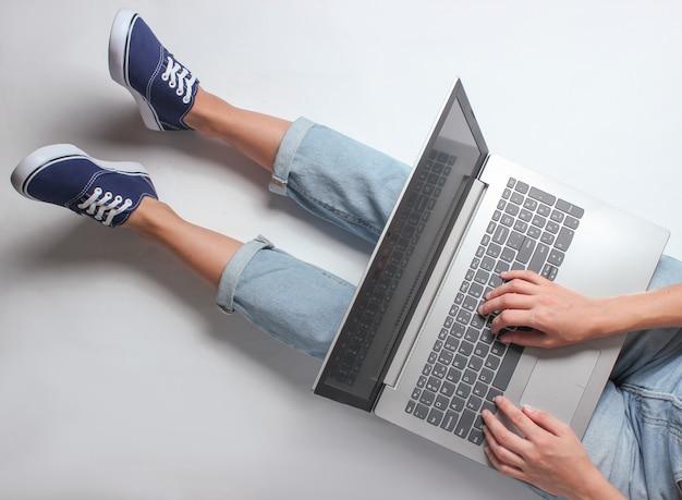 Pracownik online w miejscu pracy. fragment kobiecych nóg w dżinsach i trampkach. kobieta siedzi i używa laptopa. koncepcja niezależna. praca w domu.
