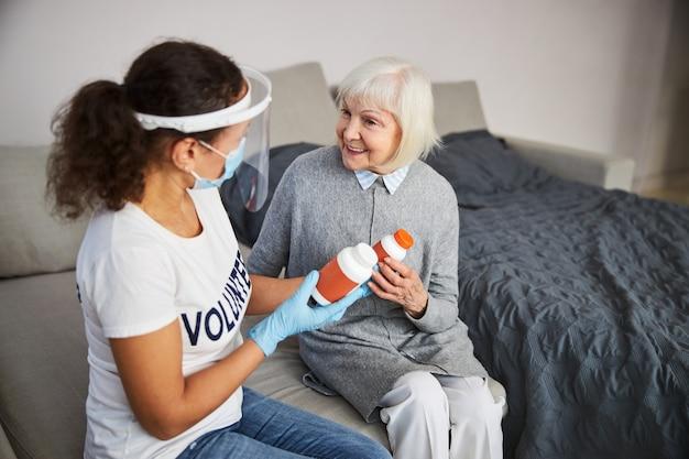 Pracownik opieki nadający starzejącej się osobie dwa warianty leków z radosnym uśmiechem na twarzy