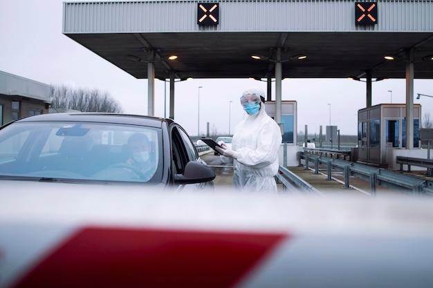 Pracownik opieki zdrowotnej w białym kombinezonie ochronnym kontrolujący pasażerów i test pcr na przejściu granicznym z powodu globalnej pandemii koronawirusa.