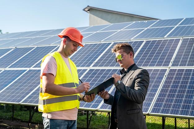 Pracownik opowiada swojemu szefowi, jak montuje się panele słoneczne, pojęcie zielonej energii