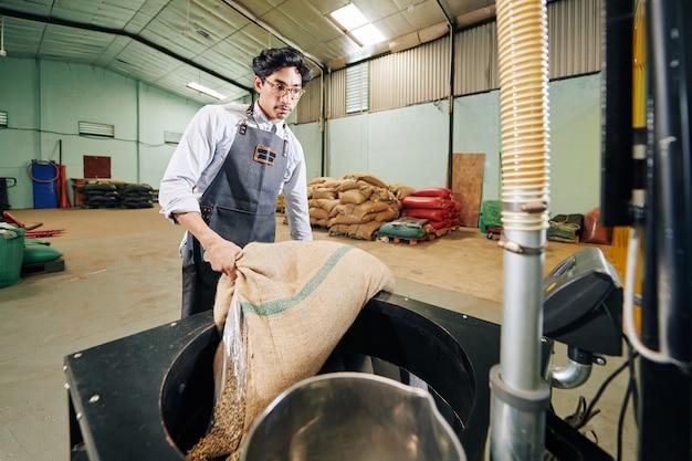 Pracownik palący ziarna kawy