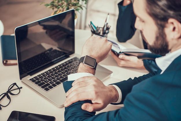 Pracownik patrzeje zegarek przy biurkiem w biurze w kostiumu.