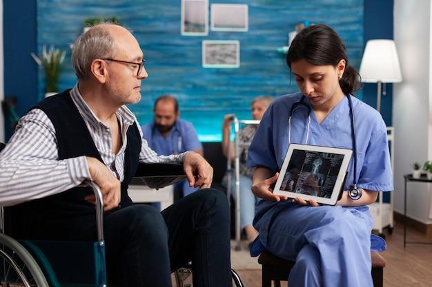 Pracownik pielęgniarki społecznej wyjaśniający emerytowi radiografię medyczną przy użyciu komputera typu tablet