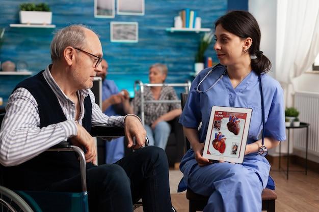 Pracownik pielęgniarki społecznej wyjaśniający kardiogram serca emerytowanemu niepełnosprawnemu starszemu mężczyźnie