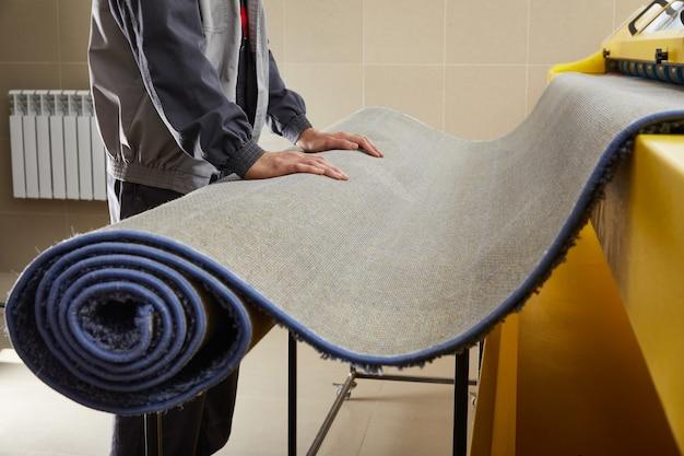 Pracownik płci męskiej czyści dywan na automatycznej pralce i suszarce w pralni