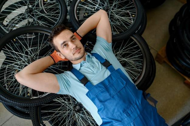 Pracownik płci męskiej leżący na stosie kół rowerowych w fabryce. linia montażowa felg w warsztacie, montaż części rowerowych, nowoczesna technologia