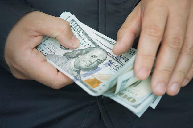 Pracownik płci męskiej liczy pensję w dolarach, zbliżenie. gotówka na kieszonkowe. napiwki w 100 banknotach. rachunkowość. pieniądze rękami