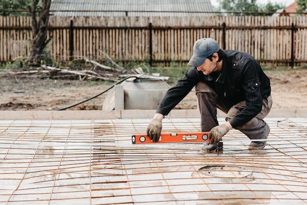 Pracownik płci męskiej mierzy poziom konstrukcji pręta zbrojeniowego na fundament domu w budowie