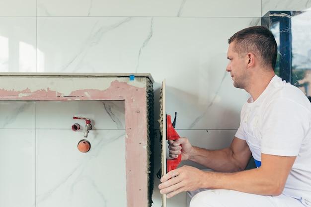 Pracownik płci męskiej montuje dużą płytkę ceramiczną w łazience