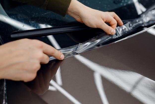 Pracownik płci męskiej montuje przezroczystą folię ochronną na masce samochodu. montaż powłoki chroniącej lakier samochodu przed zarysowaniami. nowy pojazd w garażu