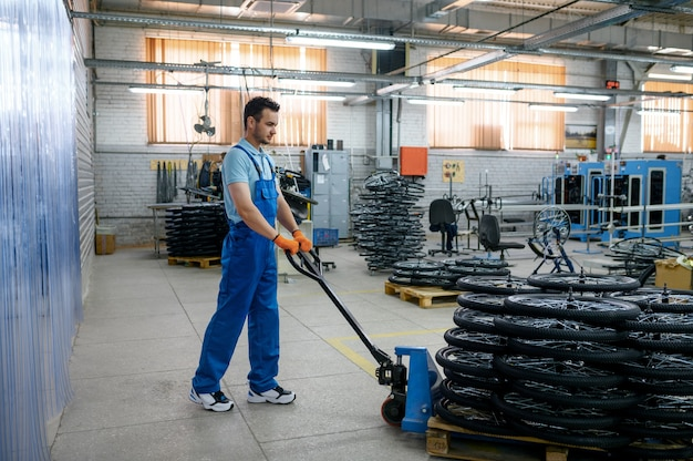 Pracownik płci męskiej niesie koła rowerowe na wózku w fabryce. linia montażowa felg w warsztacie, montaż części rowerowych, nowoczesna technologia