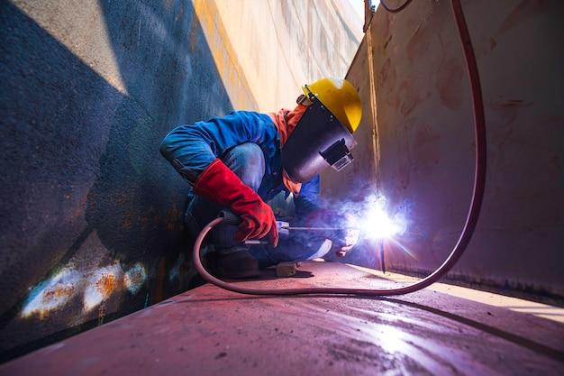 Pracownik płci męskiej noszący odzież ochronną i naprawiający spawanie przemysłowego oleju i gazu budowlanego lub zbiornika magazynowego w zamkniętych przestrzeniach.