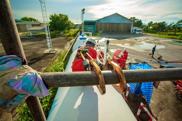 Pracownik płci męskiej noszący pierwszą uprząż bezpieczeństwa i samotny bezpieczeństwa pracujący na wysokim rusztowaniu na otwartym dachu zbiornika olejowego