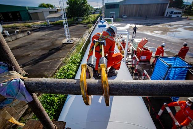 Pracownik płci męskiej noszący pierwszą uprząż bezpieczeństwa i samotny bezpieczeństwa pracujący przy wysokiej poręczy na otwartym dachu zbiornika na olej