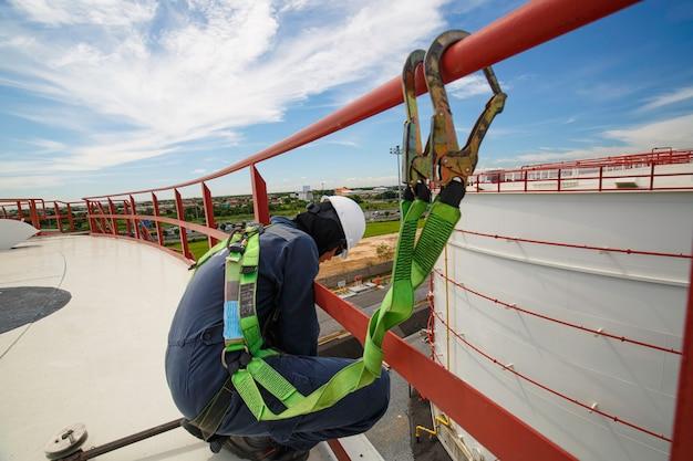 Pracownik płci męskiej noszący pierwszą uprząż bezpieczeństwa i samotny bezpieczeństwa pracujący przy wysokiej poręczy na otwartym dachu zbiornika oleju