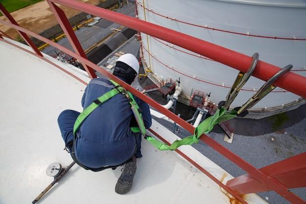 Pracownik płci męskiej noszący pierwszą uprząż bezpieczeństwa i samotny, pracujący przy wysokiej poręczy na otwartym dachu zbiornika oleju