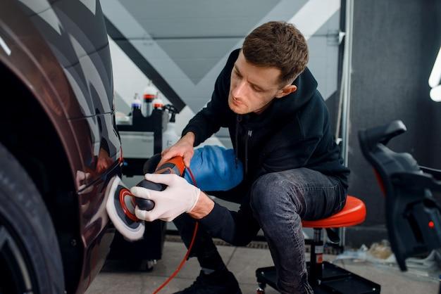 Pracownik płci męskiej poleruje zderzak za pomocą maszyny do polerowania, detal samochodu.