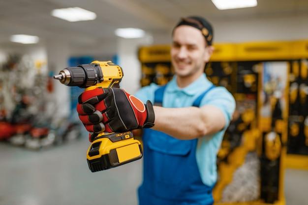Pracownik płci męskiej posiada śrubokręt zasilany bateryjnie w sklepie narzędziowym. wybór profesjonalnego sprzętu w sklepie z narzędziami, supermarkecie z narzędziami elektrycznymi