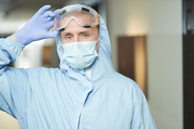 Pracownik płci męskiej przeprowadzający dezynfekcję w specjalnej odzieży ochronnej oraz w okularach. koncepcja koronawirusa i kwarantanny