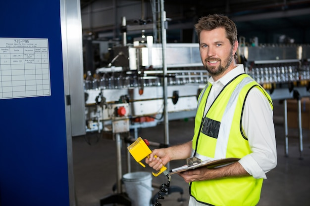 Pracownik płci męskiej przy użyciu maszyn w fabryce soków