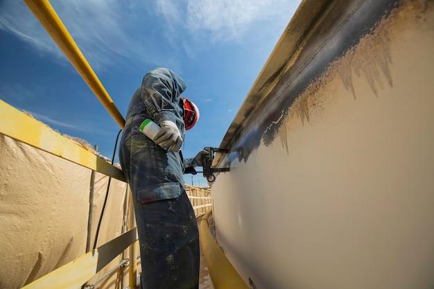 Pracownik płci męskiej przy wysokim testowym zbiorniku stalowym nakładka spoina czołowa powłoka węglowa płyta zbiornika magazynowego tło olejowe biały kontrast testu pola magnetycznego