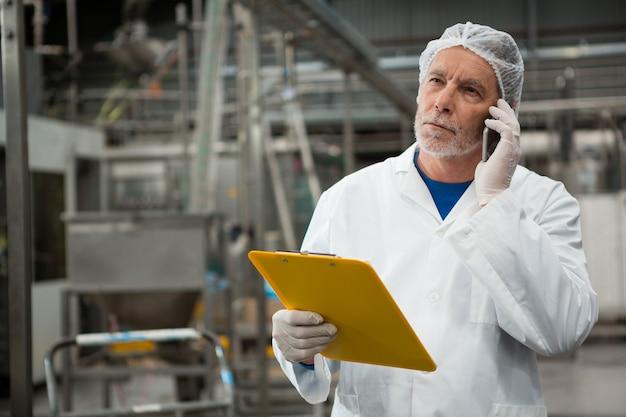 Pracownik płci męskiej rozmawia przez telefon komórkowy w fabryce zimnych napojów