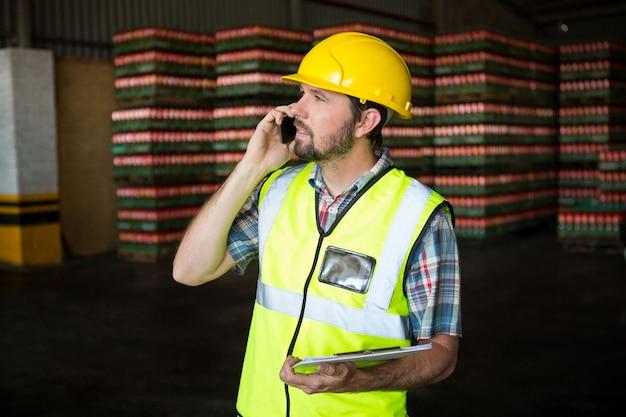 Pracownik płci męskiej rozmawia przez telefon w fabryce