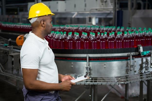 Pracownik płci męskiej sprawdzający butelki w fabryce soków