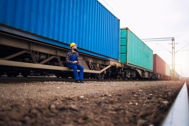 Pracownik płci męskiej sprawdzający przyczepy kolejowe z kontenerami transportowymi przed wyjazdem