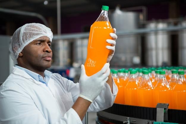 Pracownik płci męskiej sprawdzanie produktów w fabryce soków