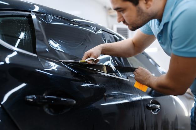 Pracownik płci męskiej trzyma arkusz folii, instalację barwienia samochodów, usługę tuningu. mechanik nakładający barwnik winylowy na szybę pojazdu w garażu, przyciemniane szyby samochodowe