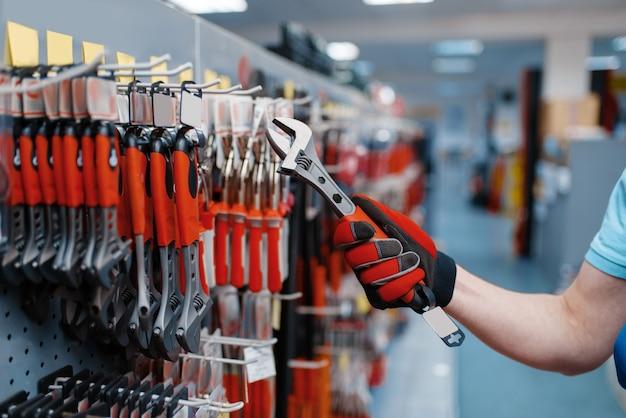 Pracownik płci męskiej w mundurze wybiera klucz nastawny w sklepie z narzędziami. wybór profesjonalnego sprzętu w sklepie z narzędziami, supermarkecie z narzędziami
