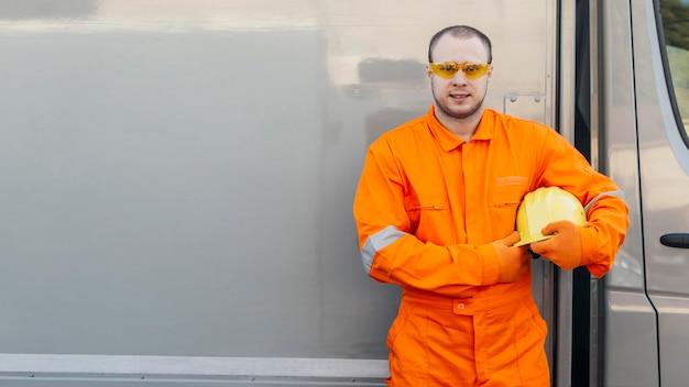 Pracownik płci męskiej w mundurze z okularami ochronnymi i miejscem na kopię