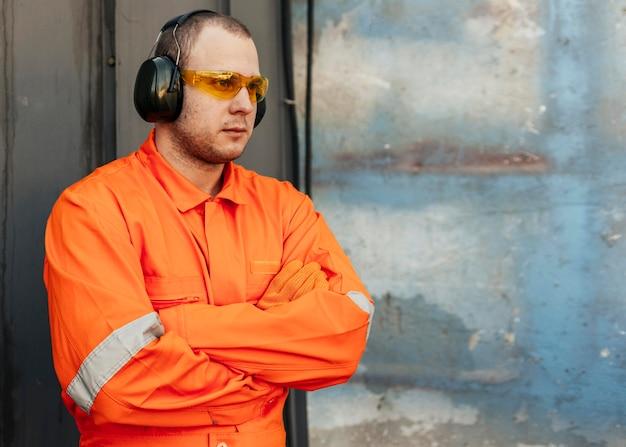 Pracownik płci męskiej w mundurze z okularami ochronnymi i słuchawkami