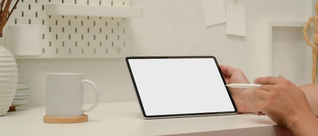 Pracownik płci męskiej wskazując na makiety tabletu z rysikiem, siedząc przy stole roboczym w biurze domowym