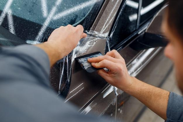 Pracownik płci męskiej wygładza folię ochronną samochodu na przednim błotniku. montaż powłoki chroniącej lakier samochodu przed zarysowaniami. nowy pojazd w garażu, procedura tuningu