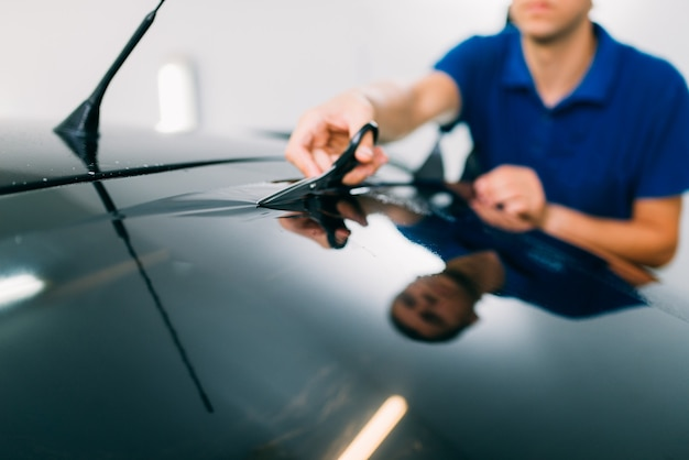 Pracownik płci męskiej z nożyczkami, proces instalacji folii barwiącej samochód, procedura instalacji przyciemnianej szyby samochodowej