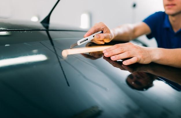 Pracownik płci męskiej z ostrzem, proces instalacji folii do barwienia samochodów, procedura instalacji przyciemnianego szkła samochodowego