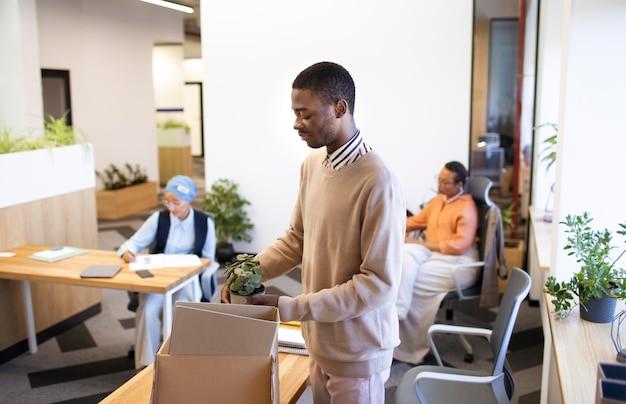 Pracownik płci męskiej z pudełkiem rzeczy w swojej nowej pracy biurowej