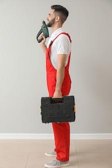 Pracownik płci męskiej z wiertłem i zestawem narzędzi w pobliżu lekkiej ściany