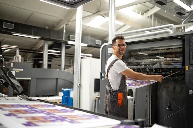 Pracownik pobierający nadruk z nowoczesnej maszyny drukarskiej w celu dopasowania kolorów i kontroli jakości.
