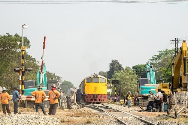 Pracownik pociągu i koparki usprawniający budowę linii kolejowej